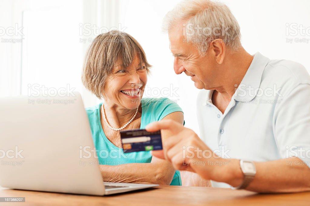 Happy senior couple buying on the internet royalty-free stock photo