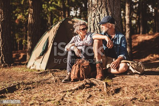 Portrait of happy senior couple sitting together under a tree on summer day. Mature man and woman near the tent, camping in forest.