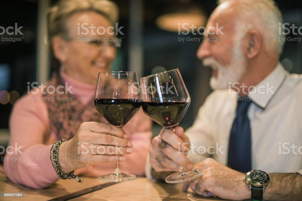Happy senior couple celebrating their love with wine. stock photo