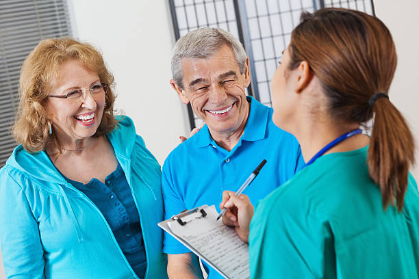 happy senior couple checking in to hospital with nurse - question mark asking doctor nurse stock photos and pictures
