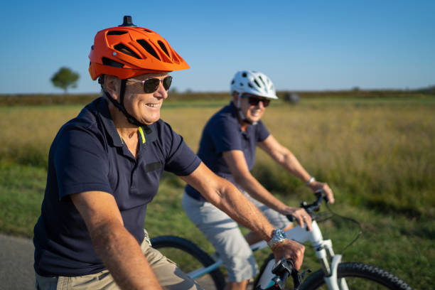 happy senior couple cycling together in rural landscape medium shot happy smiling senior man with bike helmet cycling together with his wife blurred in background ebike for elder stock pictures, royalty-free photos & images