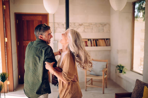 Happy senior couple dancing and laughing together at home Playful mature husband and wife having fun, celebrating, dancing and laughing together in living room husband stock pictures, royalty-free photos & images