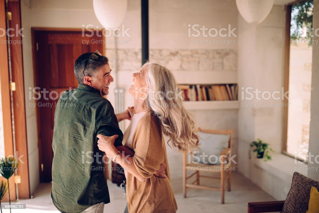 Happy senior couple dancing and laughing together at home stock photo