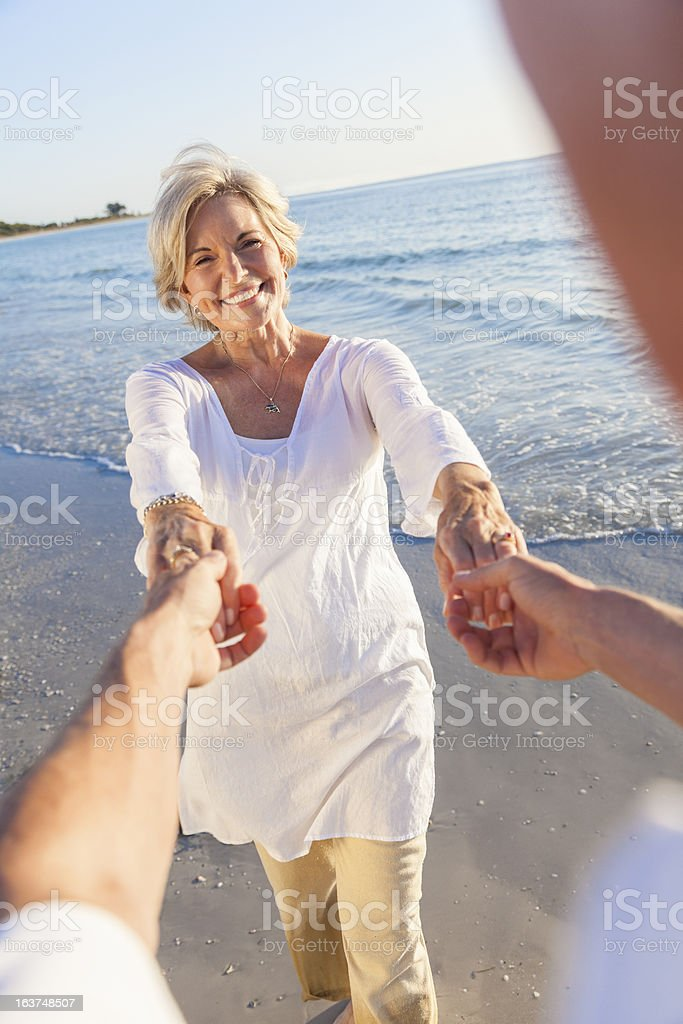 Happy Senior Couple Dancing Holding Hands on a Beach royalty-free stock photo