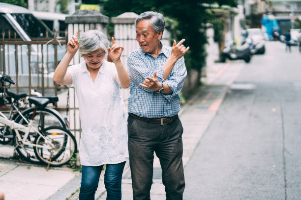 Happy senior couple dancing on street Happy senior couple dancing on street. young at heart stock pictures, royalty-free photos & images