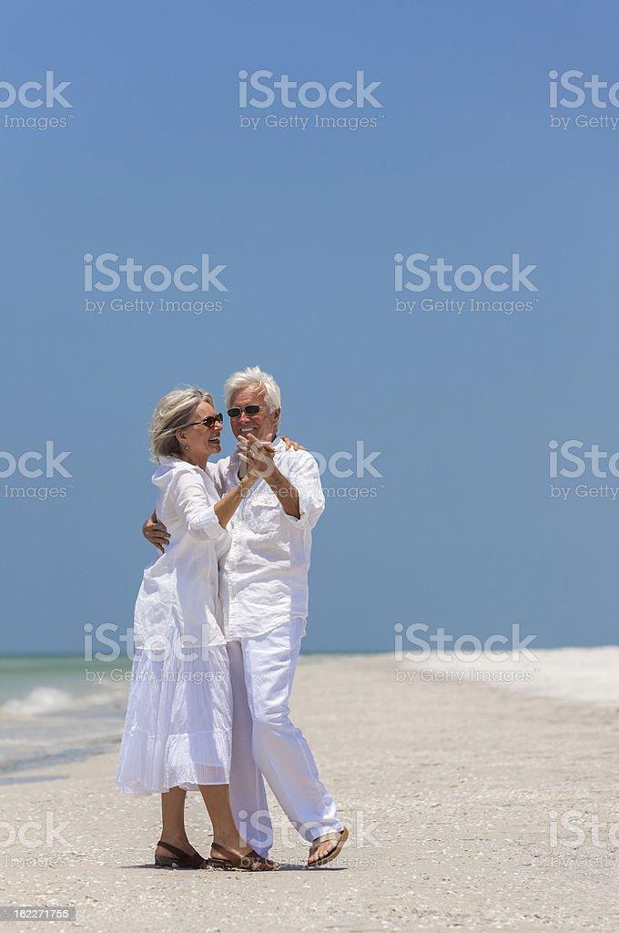 Happy Senior Couple Dancing on Tropical Beach royalty-free stock photo