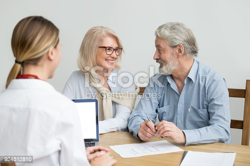 1040654052 istock photo Happy senior couple discussing house purchase at meeting with agent 924512810