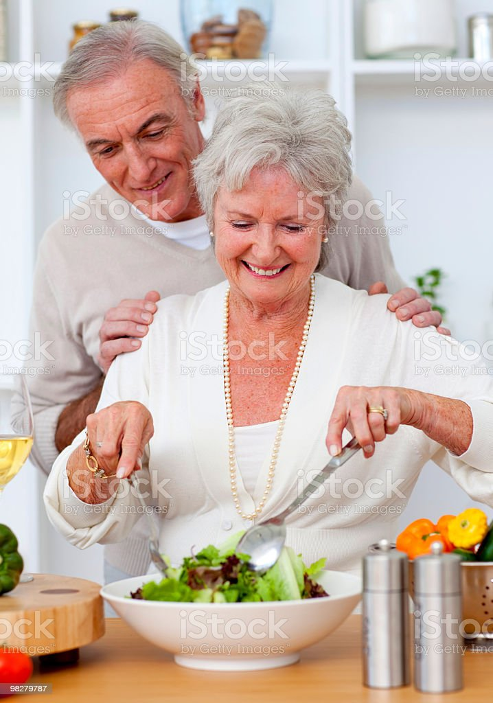 Happy senior couple eating a salad in the kitchen royalty-free stock photo