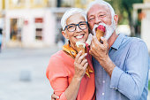 Modern and happy senior couple eating ice cream outdoor