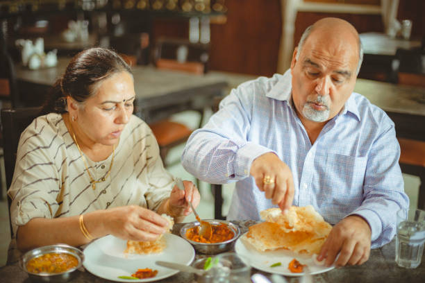 Happy senior couple eats lunch together at a restaurant. stock photo