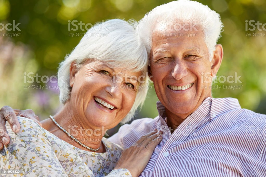 Happy senior couple embracing in garden, head and shoulders стоковое фото
