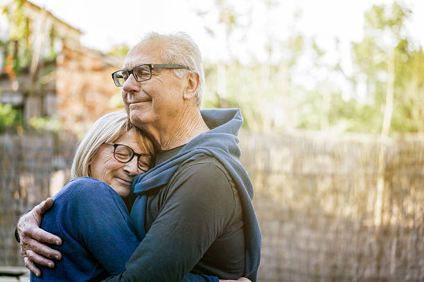 happy senior couple embracing outdoors - 60 69 years stock photos and pictures