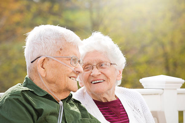 Happy Senior Couple Enjoying Conversation A happy 92 year old and his 89 year old wife enjoying eachother's company outdoors on a beautiful fall day. medical oxygen equipment stock pictures, royalty-free photos & images