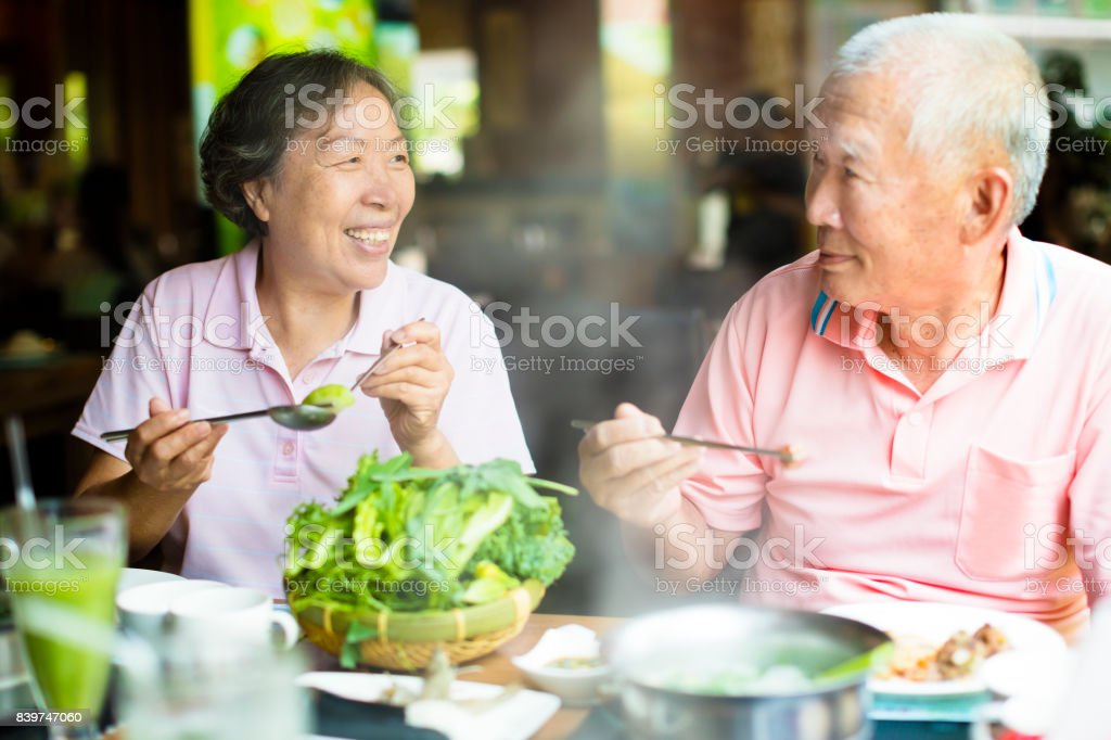 happy Senior Couple Enjoying hot pots In Restaurant stock photo