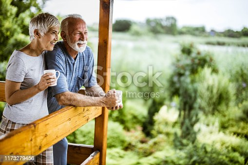 Happy mature couple having their morning coffee on a balcony and looking at view. Copy space.