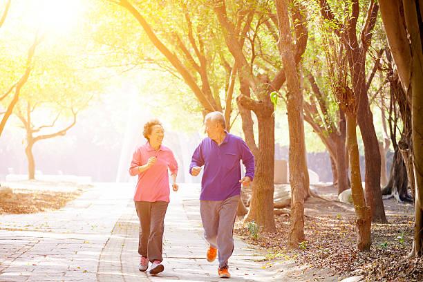 happy Senior Couple Exercising In the Park stock photo