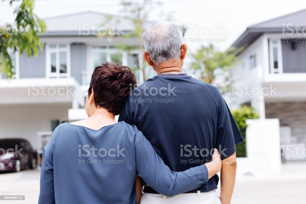 Happy senior couple from behind looking at front of house and car stock photo