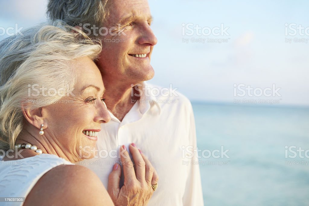 Senior Couple Getting Married In Beach Ceremony Looking At Sea Smiling