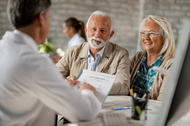Happy senior couple going through medical insurance paperwork with a doctor. Happy mature couple informing themselves about health insurance while talking to a doctor at clinic. medicare stock pictures, royalty-free photos & images