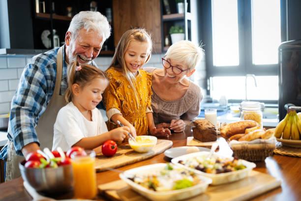 Happy senior couple having breakfast with their grandchildren at home stock photo