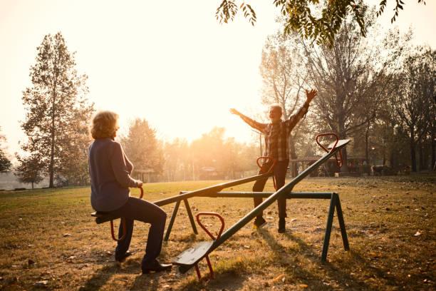 Glückliches Seniorenpaar mit Spaß auf dem Spielplatz, Reiten Wippe – Foto