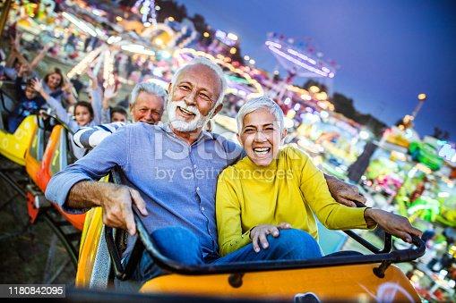 Carefree seniors having fun on rollercoaster at amusement park.