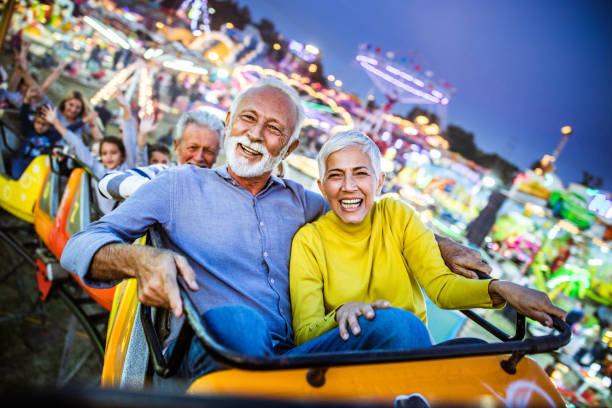 Happy senior couple having fun while riding on rollercoaster at amusement park. stock photo