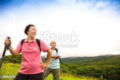 istock happy senior couple hiking on the mountain 489633076