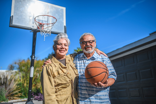 Happy Senior Couple Holding Basketball In Backyard Stock