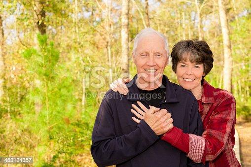 510491454 istock photo Happy senior couple hug outside at local park. 483134357