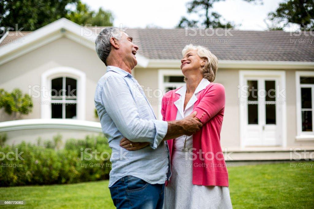 Happy senior couple hugging in yard foto stock royalty-free