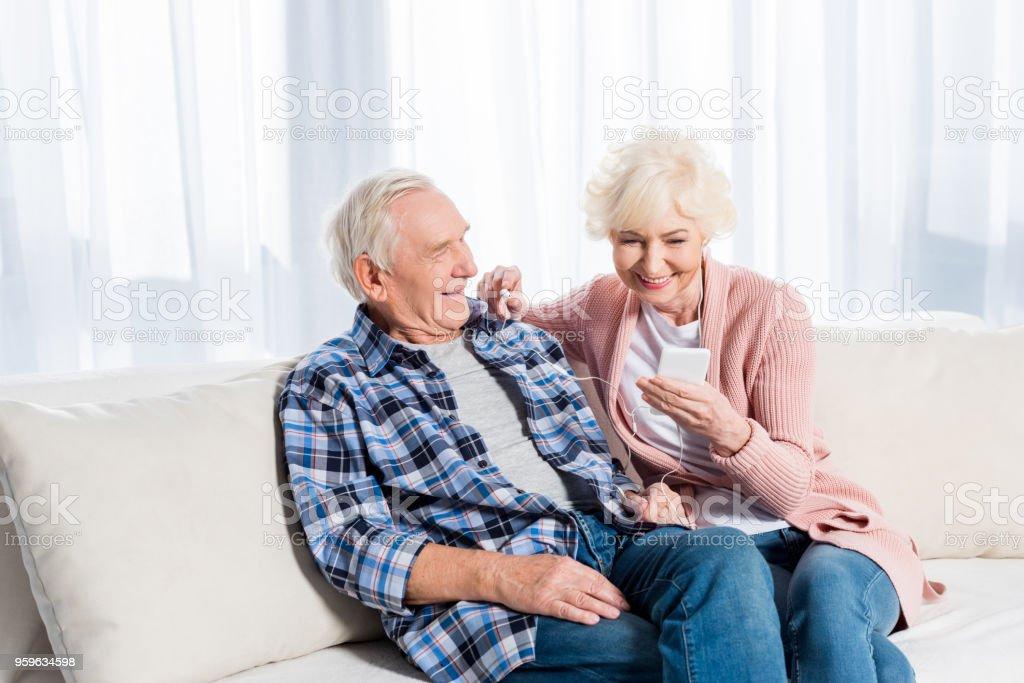 feliz pareja senior en auriculares escuchando música juntos en casa - Foto de stock de Adulto libre de derechos