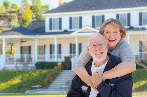 happy senior couple in front of house - senior housing stock photos and pictures