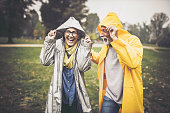 Happy mature couple covering their heads with hood during rainy day in the park.