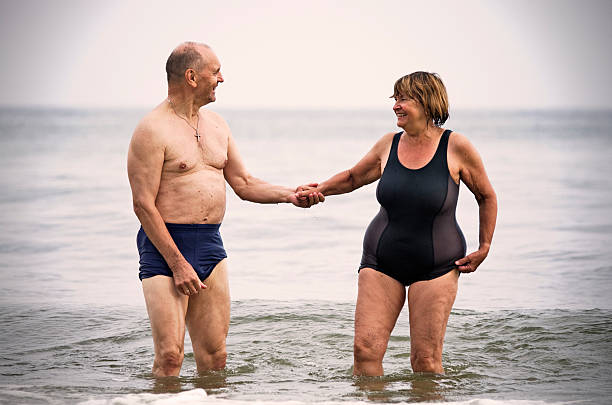 Happy senior couple in sea  wading stock pictures, royalty-free photos & images