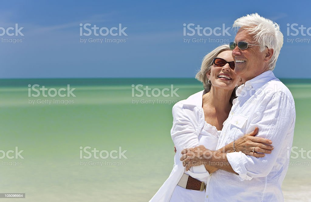 Happy senior couple in white on tropical beach stock photo
