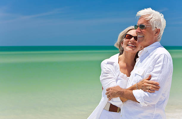 feliz casal sênior em branco na praia tropical beach - viagem de primeira classe - fotografias e filmes do acervo