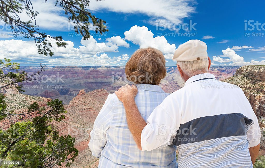 Happy Senior Couple Looking Out Over The Grand Canyon stock photo