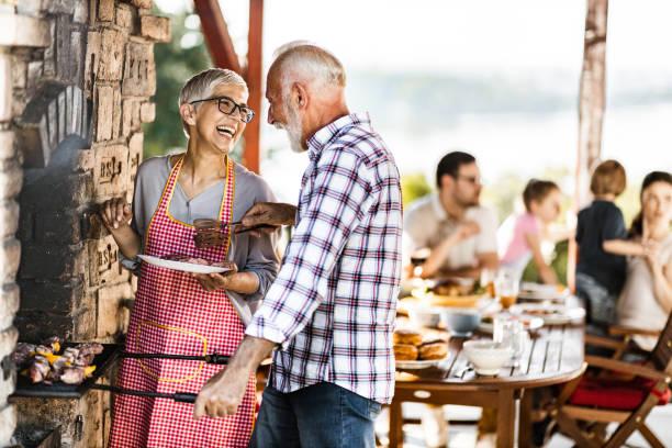feliz pareja de la tercera edad haciendo barbacoa para su familia en una terraza. - couple lunch outdoors fotografías e imágenes de stock