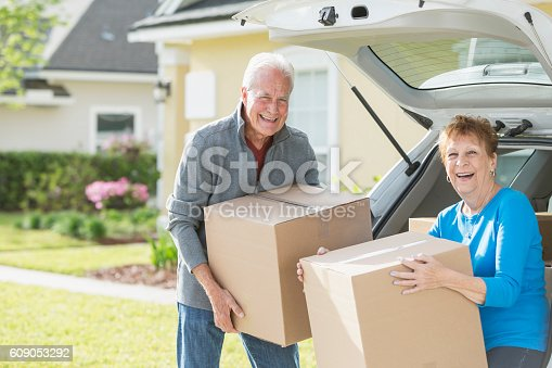 A happy senior couple moving boxes into or out of the back of their car. They are moving house, perhaps downsizing. They are looking at the camera, smiling.