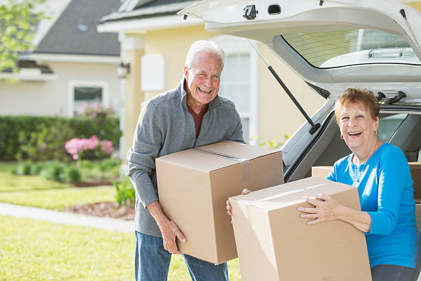 Happy senior couple moving boxes in car stock photo