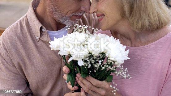 510491454istockphoto Happy senior couple nuzzling, holding flowers bunch together, anniversary date 1086727882
