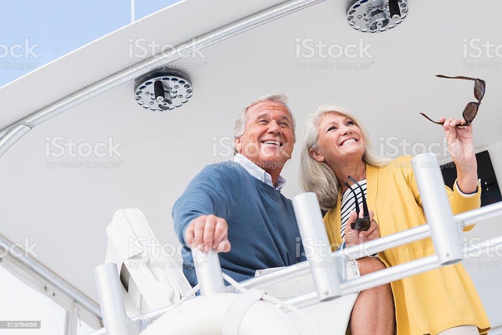 Happy senior couple on boat laughing stock photo