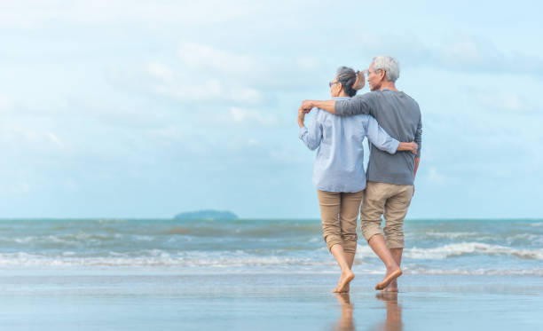 Happy senior couple on the beach. Exotic luxury resort.back view. Happy senior couple on the beach. Exotic luxury resort.back view. senior couple stock pictures, royalty-free photos & images