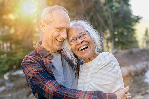 An active mixed race senior couple laugh while hiking together through a forest on a sunny day. They are on vacation and staying healthy while enjoying nature.