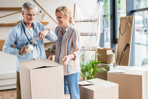 happy senior couple packing cardboard boxes during relocation - relocation stock photos and pictures