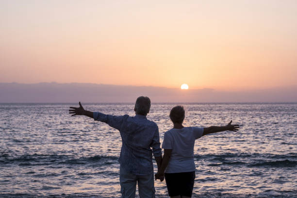 Happy senior couple people in love enjoy a sunset on the ocean holding hands - ñpve and relationship elderly summer holiday lifestyle man and woman together in happiness looking the sea stock photo