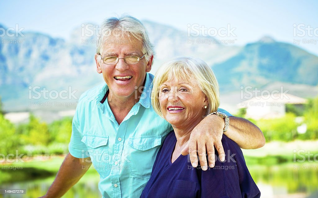 Happy senior couple Outdoor portrait of happy senior couple embracing with beautiful mountains view in the background. 60-64 Years Stock Photo