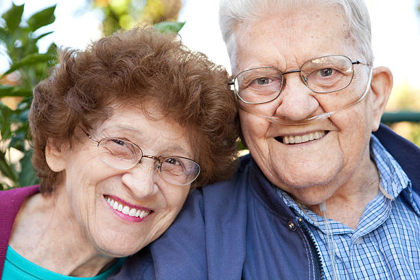 Happy Senior Couple A mid-80's couple smiling together. oxygen tube stock pictures, royalty-free photos & images