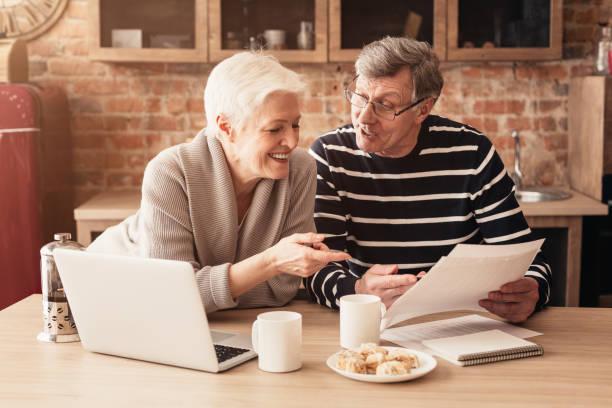 happy senior couple planning family budget junto con laptop and papers - planificación financiera fotografías e imágenes de stock